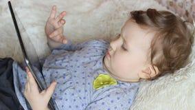Grappig kind met een tablet in zijn handen die op beeldverhalen op Internet letten stock videobeelden
