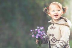 Grappig kind openlucht bij de holdingsbloemen van het bloemengebied Het seizoen van de herfst Weg in dalingsbos Stock Foto