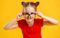 Grappig kindmeisje in glazen op gekleurde achtergrond Royalty-vrije Stock Foto