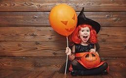Grappig kindmeisje in heksenkostuum voor Halloween met pompoen Ja Stock Foto's