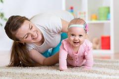 Grappig kruipend babymeisje met moeder Royalty-vrije Stock Foto's