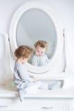Grappig leuk babymeisje die op haar gedachtengang in een witte slaapkamer letten Stock Foto