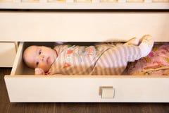 Grappig leuk babymeisje in een lade Stock Foto