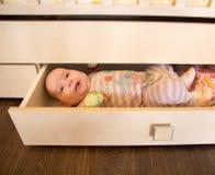 Grappig leuk babymeisje in een lade Stock Foto's