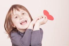 Grappig leuk portret van weinig kindmeisje die rood hart houden als symbool van liefde en amorousness royalty-vrije stock afbeelding