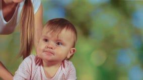 Grappig leuk weinig babymeisje die op schommeling berijden en met moeder, langzame motie spelen stock footage