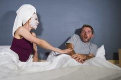 Grappig levensstijlportret van mens en vrouw die bizar echtpaar met vrouw in hoofdhanddoek en make-upgezichtsmasker de kenmerken  stock afbeelding