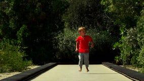 Grappig loopt weinig jongen en springt op het trampolinespoor in het park stock videobeelden