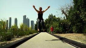 Grappig loopt weinig jongen met mamma en springt op het trampolinespoor in het Park stock footage
