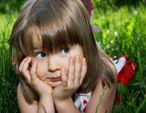 Grappig meisje dat in groen gras ligt Royalty-vrije Stock Fotografie