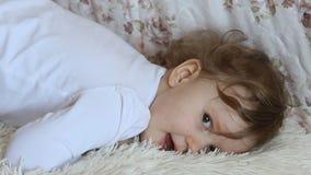 Grappig meisje die in bed het glimlachen liggen stock footage