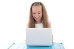 Grappig meisje die die computer met behulp van op wit wordt geïsoleerd Stock Afbeeldingen