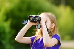 Grappig meisje die door verrekijkers op zonnige de zomerdag kijken royalty-vrije stock foto