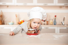 Grappig meisje die met chef-kokhoed cake eten stock foto