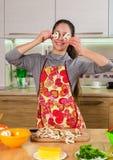 Grappig meisje die met paddestoelenplakken op ogen de pizza maken Stock Afbeeldingen