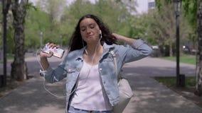 Grappig meisje die onderaan straat en het dansen het luisteren aan muziek op hoofdtelefoons lopen stock videobeelden