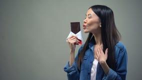 Grappig meisje die van zoet aroma die van chocoladereep genieten, het, vrouw kussen die dieet houden stock videobeelden