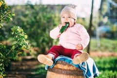 Grappig meisje die verse komkommer in de tuin in de lente eten stock afbeelding