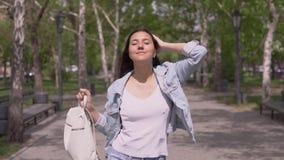 Grappig meisje in een goede stemming met lang haar met een rugzak in hand gangen onderaan de straat in zonnige grappig weer en da stock videobeelden