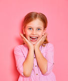 Grappig meisje in een roze overhemdsholding zelf voor gezicht op roze achtergrond stock foto
