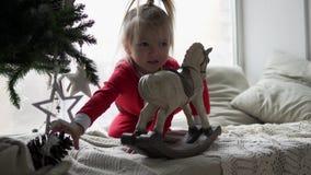 Grappig meisje het spelen speelgoed door de Nieuwjaarboom stock videobeelden