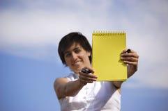 Grappig meisje met een gele noteb Stock Afbeelding
