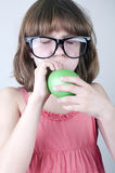 Grappig meisje met kuddezonnebril die een ballon blazen Stock Afbeelding