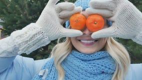 Grappig meisje met twee mandarins in plaats van ogen stock videobeelden