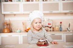 Grappig meisje met van de chef-kokhoed en mond hoogtepunt van cake royalty-vrije stock afbeeldingen