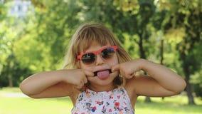 Grappig meisje met zonnebril die gezichten maken en pret hebben; langzame motie stock video