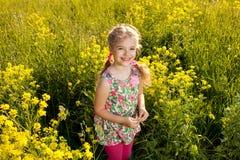 Grappig meisje onder gele wildflowers Stock Afbeelding