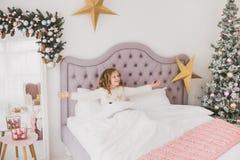 Grappig meisje op Kerstmisochtend in wit huisbinnenland Royalty-vrije Stock Foto's