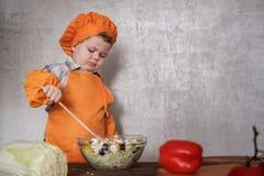 Grappig mengt weinig Europese jongen gekleed als een chef-kok een Griekse salade met een lepel royalty-vrije stock afbeeldingen