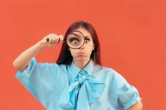 Grappig Nieuwsgierig Meisje die een Vergrootglas houden stock foto's