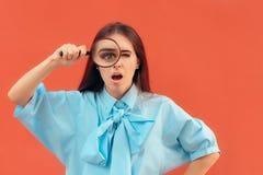 Grappig Nieuwsgierig Meisje die een Vergrootglas houden stock afbeeldingen
