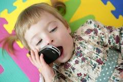 Grappig peutermeisje dat mobiele celtelefoon spreekt Stock Foto's