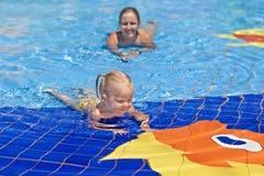 Grappig portret van het vrolijke babymeisje zwemmen in waterpark stock fotografie