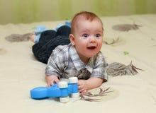 Grappig tevreden weinig jongen die op het bed met zijn stuk speelgoed liggen Stock Afbeeldingen