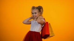 Grappig tienermeisje die en het winkelen weinig shopaholic zakken tonen, kortingen knipogen stock footage