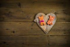 Grappig varkenspaar van zout deeg op een hart met houten achtergrond Stock Foto's