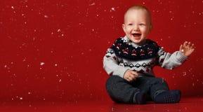 Grappig weinig baby die warme gebreide Kerstmissweater dragen bij studio op koude de winterdag Het sneeuwt royalty-vrije stock afbeeldingen