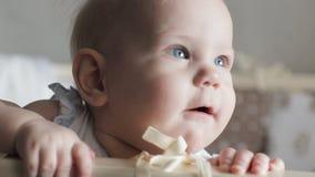 Grappig weinig en baby die glimlachen lachen Een leuke baby onderzoekt de camera stock video