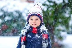 Grappig weinig jong geitjejongen die in kleurrijke kleren in openlucht tijdens sterke sneeuwval spelen Stock Afbeelding