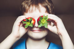 Grappig weinig jongen die een aardbei houden Royalty-vrije Stock Foto