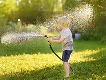 Grappig weinig jongen die met tuinslang spelen in zonnige binnenplaats Kleuterkind die pret met nevel van water hebben stock foto