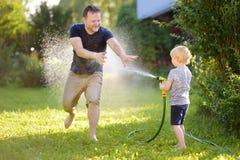 Grappig weinig jongen met zijn vader die met tuinslang spelen in zonnige binnenplaats Kleuterkind die pret met nevel van water he stock afbeeldingen