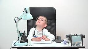 Grappig zitten weinig kind arts met grote oogglazen en stethoscoop op zijn kantoor, echte beroeps stock footage