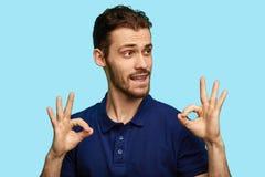 Grappige aantrekkelijke mens die ringsteken toont stock fotografie