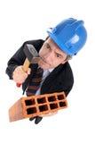 Grappige architect met een hamer en een baksteen stock foto