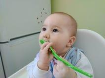 Grappige baby die een grote lepel van havermoutpap eten royalty-vrije stock fotografie